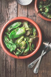 Fried peppers Pimientos de Padron or green pimientos in a traditional Spanish tapa bowl, with salt, on a rustic wooden background, top view. Spanish tapas or appetizer disch