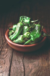Fried peppers Pimientos de Padron or green pimientos in a traditional Spanish tapa bowl, with salt, on a rustic wooden background, selected focus. Spanish tapasor appetizer disch