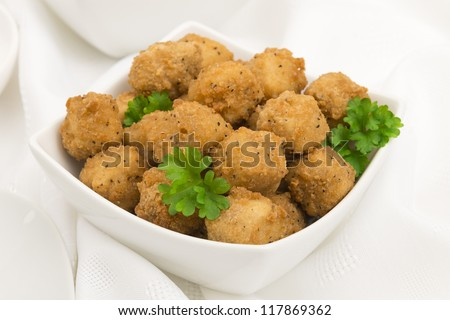 Fried Popcorn Chicken - Battered deep fried chicken balls on a white background. Close up.