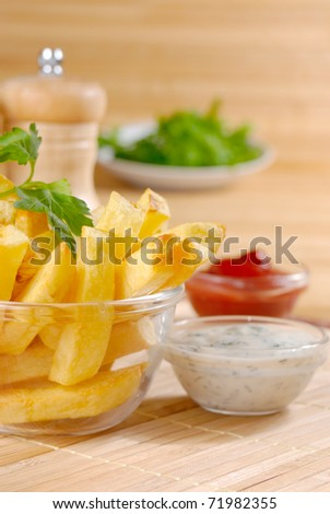Fried potato chips in the glass bowl on the wooden table
