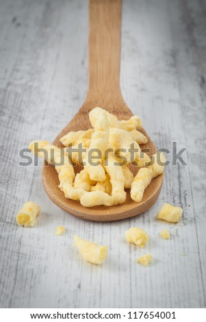 Fried potato chips on a wooden spoon