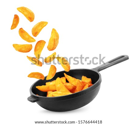 Fried potato wedges flying in pan isolated on white Stock photo ©