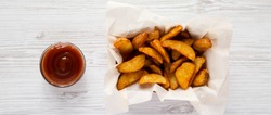 Fried potato wedges in paper box and barbecue sauce on a white wooden background. Overhead, top view, from above.