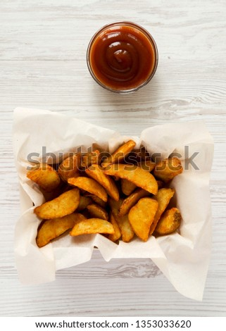 Fried potato wedges in paper box and barbecue sauce on a white wooden table, top view. Overhead, overhead, flat lay. #1353033620