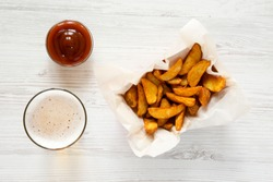 Fried potato wedges in paper box, barbecue sauce and glass of cold beer on a white wooden surface, top view. Flat lay, overhead.