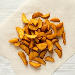 Fried potato wedges on a white wooden background, top view. From above, overhead. Close-up.
