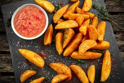 Fried potato wedges with hot salsa sauce, herbs on stone board.