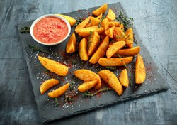 Fried potato wedges with hot salsa sauce, herbs on stone board
