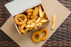 fried potatoes and onion rings in a takeaway box. top view.