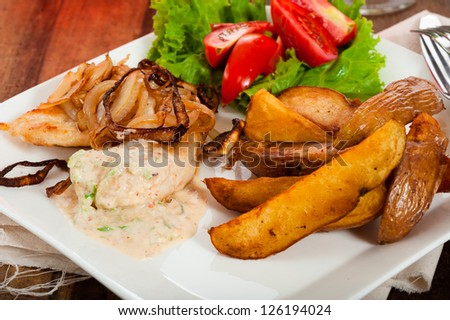 fried potatoes chicken dish with tomatoes salad and a spicy yogurt sauce.