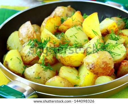 fried potatoes in a pan with herbs