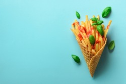 Fried potatoes in waffle cones on blue background. Hot salty french fries with tomato sauce, basil leaves. Fast food, junk food, diet concept. Top view. Minimal style. Pop art design, creative concept