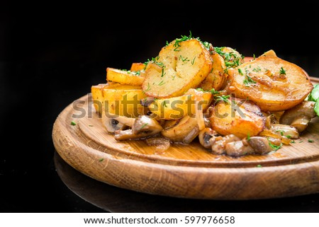 Fried potatoes with mushrooms and vegetables on a wooden board #597976658
