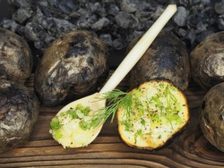 Fried potatoes with skin baked in wood charcoal and wooden spoon on the kitchen board, flat layout. Healthy grilled vegetables with potassium for dietary and vegetarian meals, cooked over a campfire