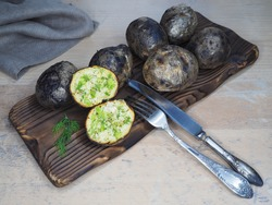 Fried potatoes with skin baked in wood charcoal, fork and knife on the kitchen board, flat layout. Healthy grilled vegetables with potassium for dietary and vegetarian meals, cooked over a campfire