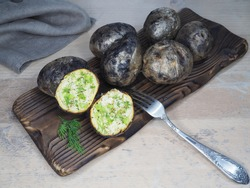 Fried potatoes with skin baked in wood charcoal, fork on the kitchen board, closeup, flat layout. Healthy grilled vegetables with potassium for dietary and vegetarian meals, cooked over a campfire