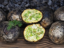 Fried potatoes with skin baked in wood charcoal on the kitchen board, closeup, flat layout. Healthy grilled vegetables with potassium for dietary and vegetarian meals, cooked over a campfire