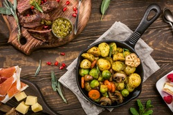 Fried potatoes with vegetables and herbs on wooden background. Healthy food concept. Overhead shot.