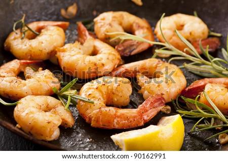 fried prawns with fresh rosmarin and lemon juice - stock photo