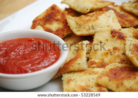 Fried Ravioli on White Plate With a Bowl of Marinara Sauce - stock photo