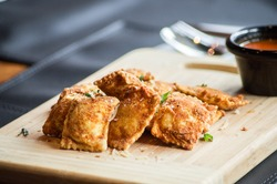 Fried Ravioli served on wooden board on a table accompanied natural tomato sauce.