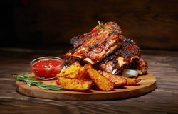 Fried ribs with rosemary, potatoes rustic, onion, sauce on wooden round Board. Dark background. Place for text, copyspace
