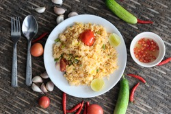 fried rice in the white plate with chili sauce in while cup,tomato,garlic,red chili,cucumber,fork and spoon on wooden.
