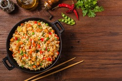 Fried rice with chicken. Prepared and served in a wok. Natural wood in the background. Top view.