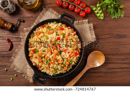 Shutterstock Fried rice with chicken. Prepared and served in a wok. Natural wood in the background. Top view.