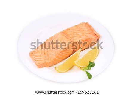 Fried salmon fillet on plate with lemon. Isolated on a white background.