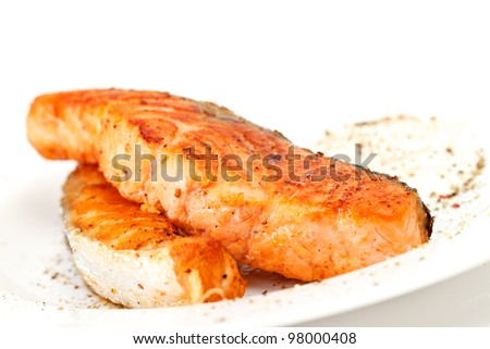 Fried salmon fillets with sauce on white plate - stock photo
