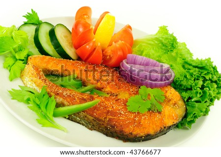 Fried salmon steak garnished with poppy seeds for flavor and decorated with green salad and herbs