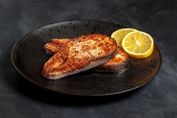 Fried salmon steak, healthy lunch dish. Roasted trout steak closeup, omega 3 nutrition appetizing with lemon on plate. Fatty norwegian salmon slice, restaurant entree concept, above side