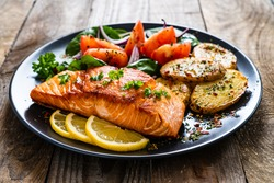 Fried salmon steak with potatoes and vegetables on wooden table