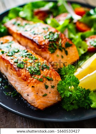 Fried salmon steaks with vegetables on wooden table