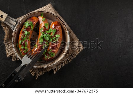 Fried sausage on an old pan on a black background #347672375