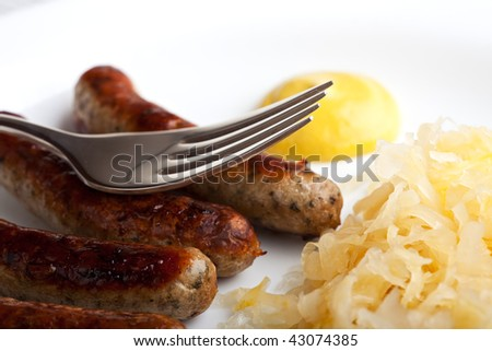 fried sausages,mustard and sauerkraut on a plate with a fork