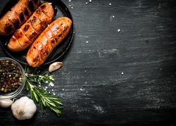 Fried sausages with garlic and herbs in a pan. On the black Board.