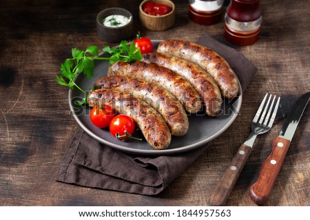 Fried sausages with spices, sauce, tomatoes and parsley in a ceramic plate on a brown wooden table Stock photo ©