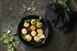 Fried scallops with butter lemon spicy sauce in cast-iron pan served with green salad and textile napkin over old dark metal background. Top view, space