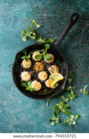 Fried scallops with butter lemon spicy sauce in cast-iron pan served with green salad over turquoise texture background. Top view, copy space