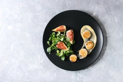 Fried scallops with lemon, figs, sauce and green salad served on black plate over gray texture background. Top view, copy space. Plating, fine dining