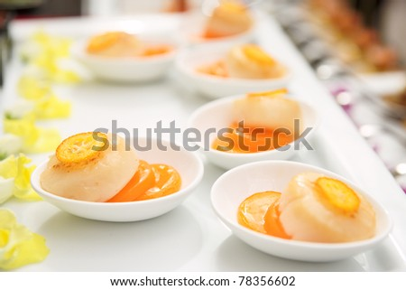 Fried scallops with orange jam on plate, closeup