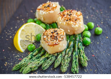 Fried scallops with sesame seeds, asparagus, lemon and green peas on a black plate. Selective focus