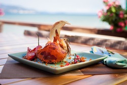 Fried sea crab served with lettuce, bread and sauce in chili pepper on beach