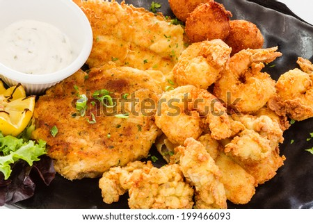 Fried seafood platter with fish, shrimp, oysters, hush puppies, and a crab cake.