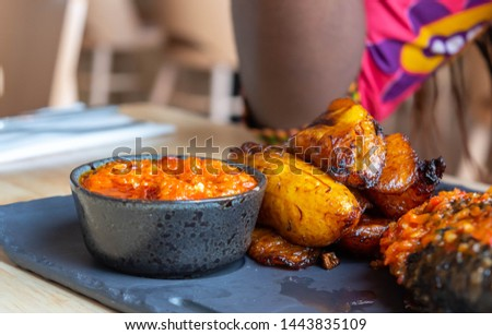 Fried slices of ripe plantain and chilli sauce eaten as snack or a dishes in Nigerian, African and South American countries  plantain slice. Platanos Maduros Foto stock ©