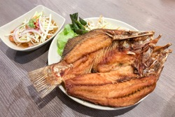 Fried Snapper fish on plate with sauce