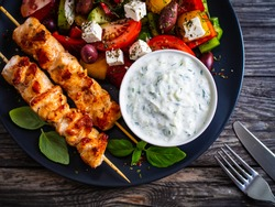 Fried souvlaki, greek salad and tzatziki on wooden table