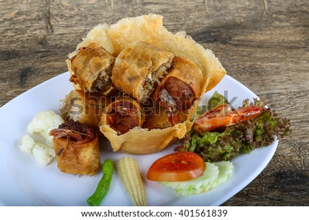Fried spring rolls in eatable basket with salad leaves #401561839